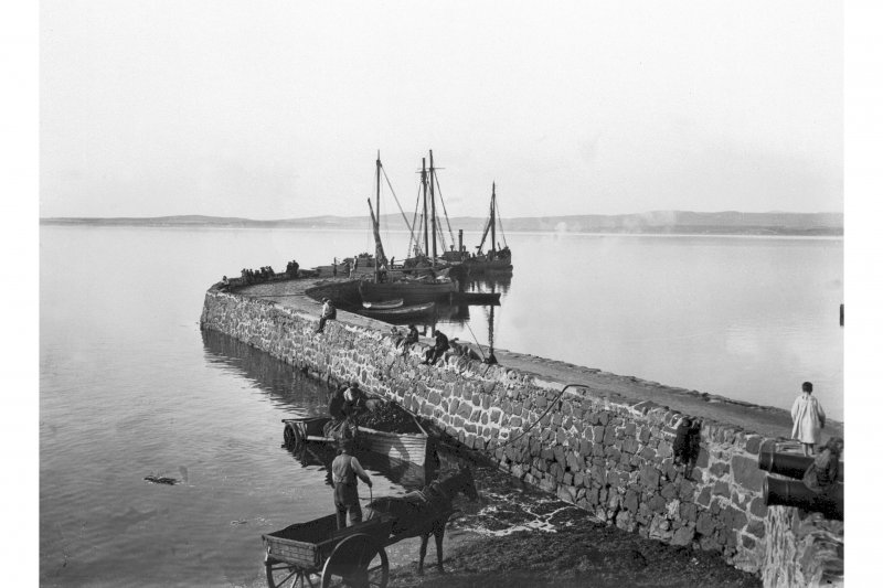 Bowmore Distillery, Bowmore, Islay. View of ship-to-shore delivery of coal to jetty by means of a small boat and cartage.