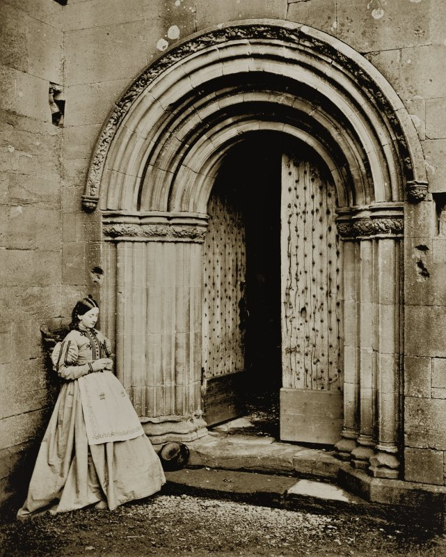 View of lady outside the North cloister doorway at Melrose Abbey.