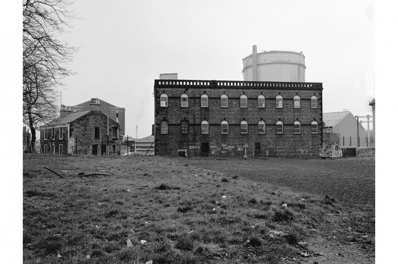 Paisley Gasworks View of 3-storey, 9-bay building with round-headed windows (foreground) and gas-holder (background)