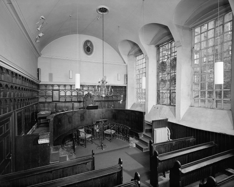 Interior-view from West of chapel showing wooden panelling and stained glass panels in windows.