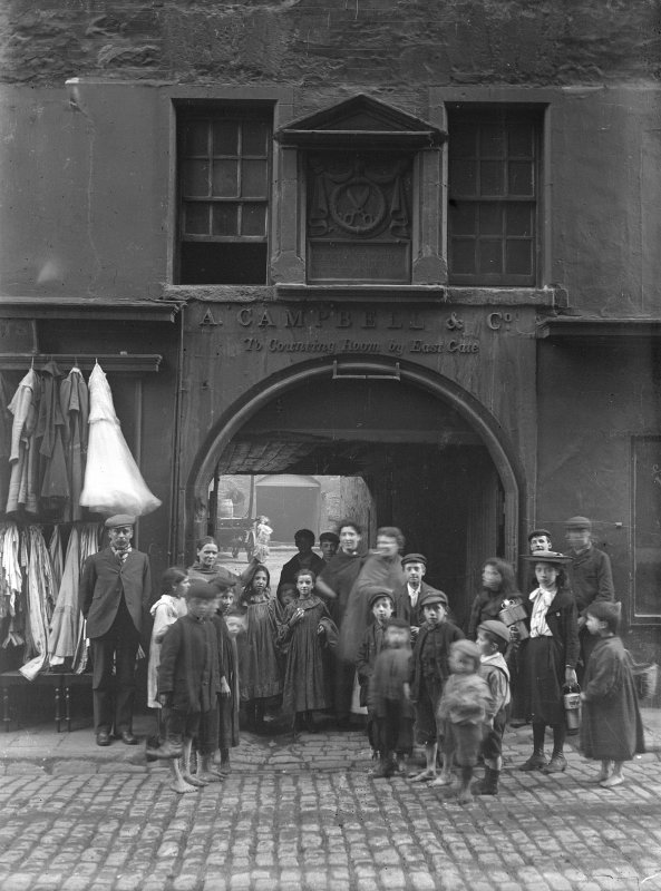 General view of main entrance wynd with group of men, women and children standing in front.