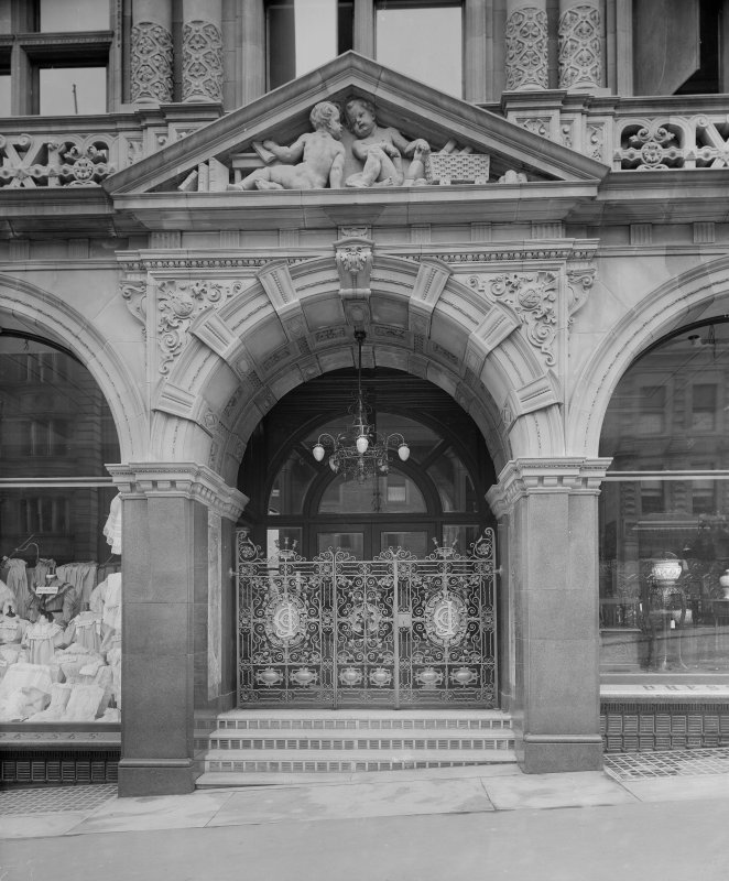 Detail of entrance doorway showing carved stonework and wrought iron gates. Jenners, Princes Street, Edinburgh.