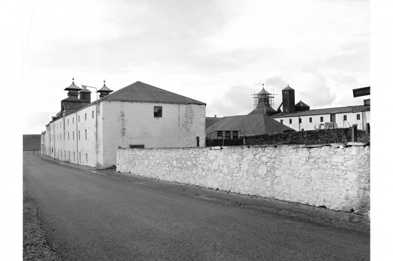 Islay, Ardbeg Distillery General view from NNE showing NNW and NE fronts of malt barn which is 11 bays long with the other malt barn in distance