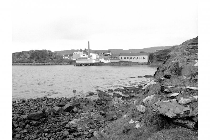 Islay, Lagavulin Distillery Distant view from SE showing S front of distillery with pier in foreground