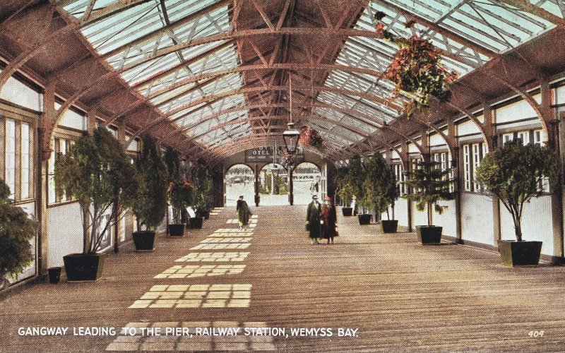 Coloured postcard view of walkway leading to pier.