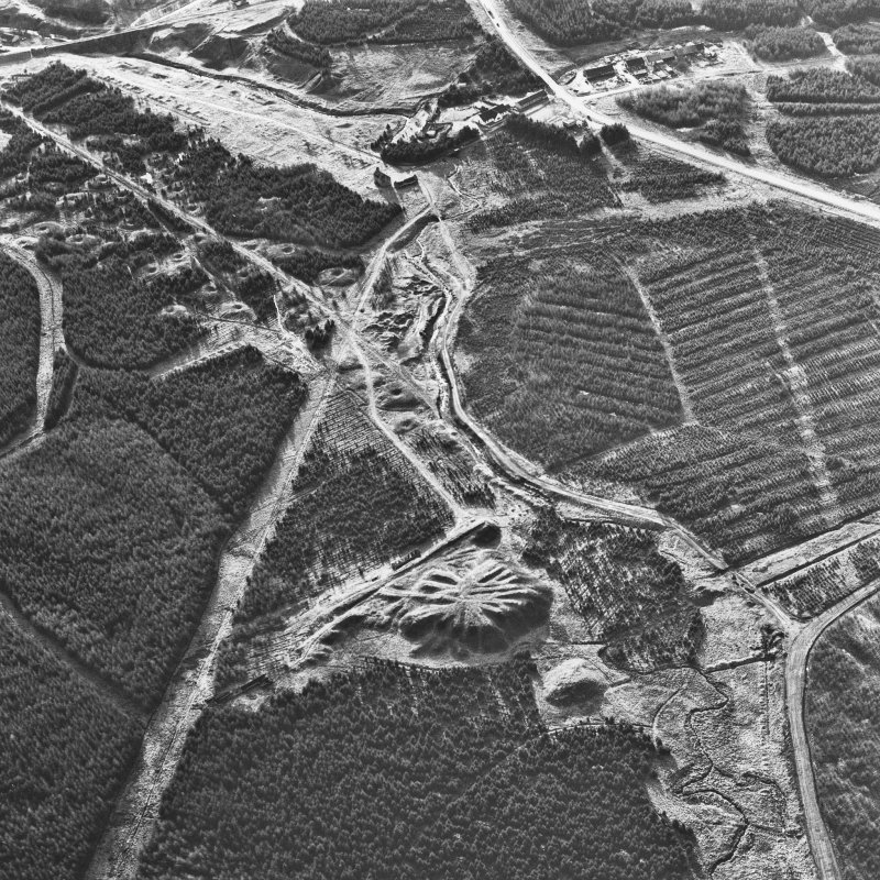 Scanned image of oblique aerial view, taken from the NE, showing the bings of two coal mines at the bottom, and the remains of ironworks, workers' rows, lime kilns, coke ovens and buildings across the remainder of the photograph, including a large area of bell pits in the centre and top left-hand corner.