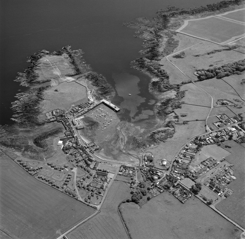 Oblique aerial view, taken from the N, centred on the village and harbour, and showing Isle Head fort and the remains of St. Ninian's Chapel in the top left-hand corner of the photograph.