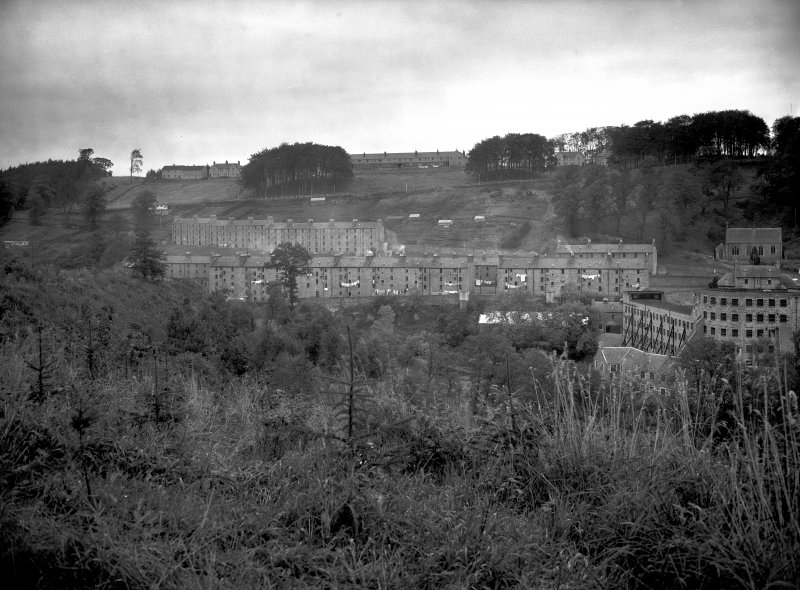 View of New Lanark from the South bank of the Clyde showing Long Row, Braxfield Row and Mantilla Row.  Also shows un-roofed and propped shell of Mill No.1 to far right of view.