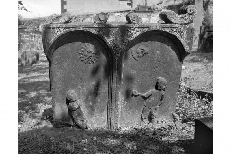 View of headstone for J.P. C.B., 1763: two panels with a figure in each, sun over left figure, moon over right.