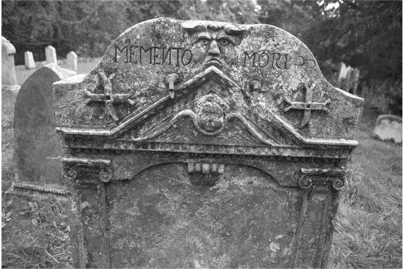 Glencorse old parish church West face, detail of gravestone of Patrick Proudfoot and Janet Hunter d.1742; 'Green Man' face and 'MEMENTO MORI' legend above a tympanum filled by a winged cherub.