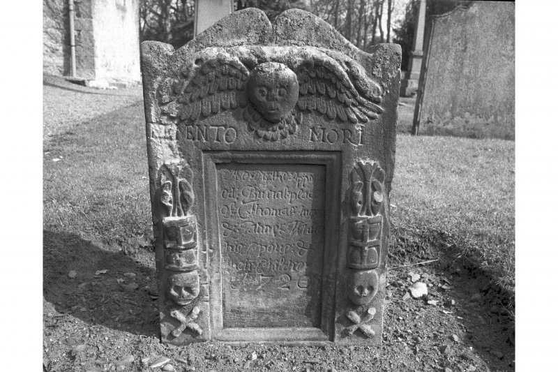 View from W of gravestone commemorating Thomas Angus and Jean White, d.1720; sunken inscription panel flanked by emblems of mortality, winged cherub at top with 'MEMENTO MORI' inscription beneath.