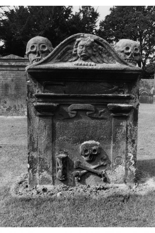 View of gravestone of David Sevitch. Skulls on top slopes, winged cherub in pediment, tailor's 'goose' and shears.