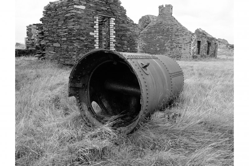 Belnahua Slate Quarry View of disused upright boiler, schoolhouse in background