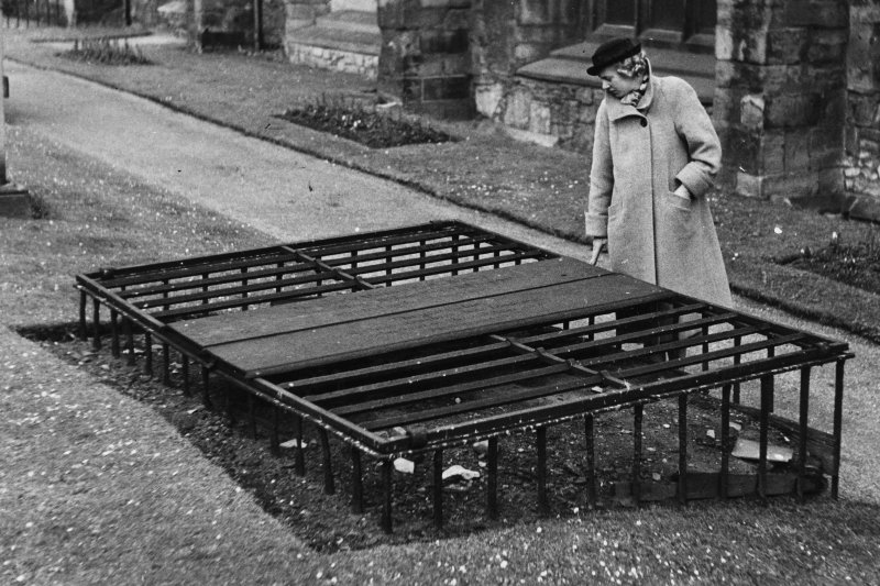 "Detail of example of mortsafe in Greyfriars Churchyard Typed passage on verso reads ""A Relic of Body Snatching in Greyfriars Churchyard, Edinburgh.  From 1771 till the trial in 1828 of Burke (of the firm of Burke and Hare) the Scottish capital was notorious for 'the most horrid and unchristian actions of the grave makers, their raising and selling of the dead, abhorred by Turks and heathens'.  One provision made to guard against this practise was to cover over the graves with heavy iron bars, putting the gravestones themselves on top of this grille work, as shown."""