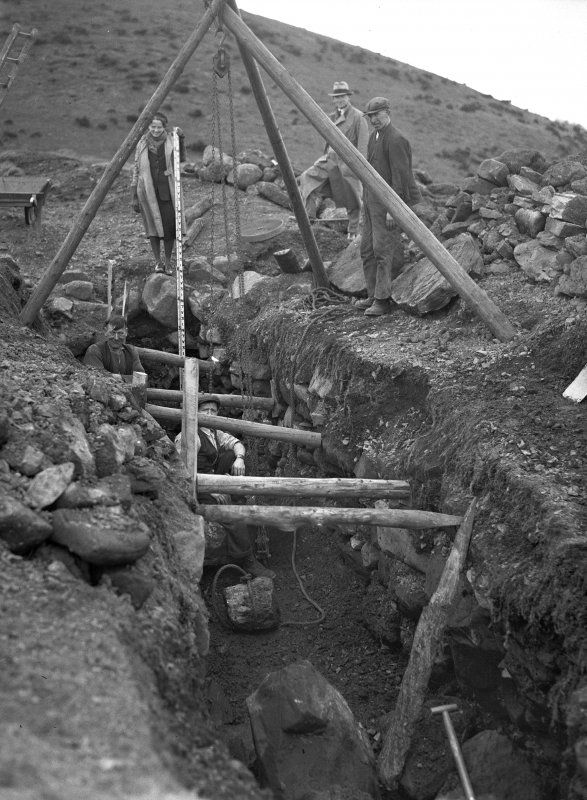 View of Castle Law fort and settlement showing the souterrain during the excavation in 1932. Dr Margaret E C Stewart is in the photograph.