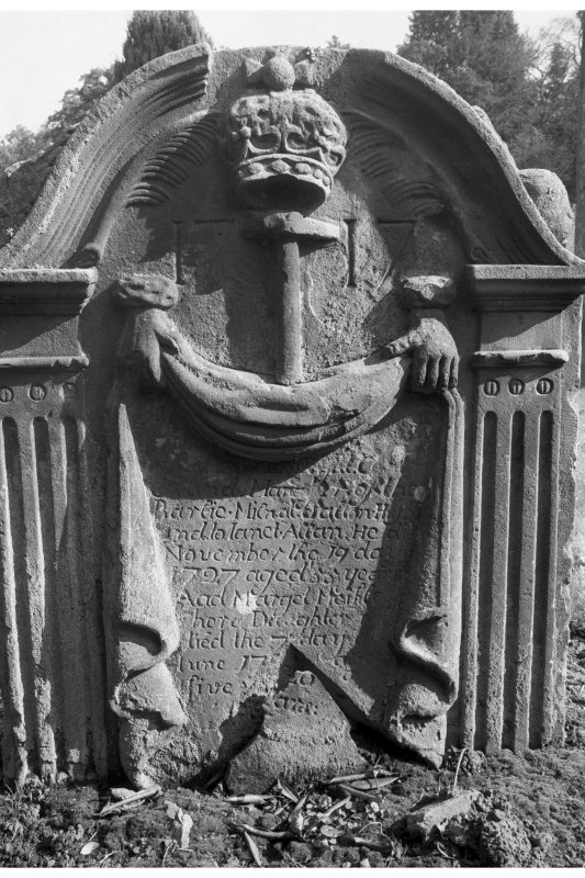 Humbie churchyard. Hugh Meikle d.1727. Royal crown and hammer flanked by palm fronds with date 1717. Inscription framed by drapery held by two hands.