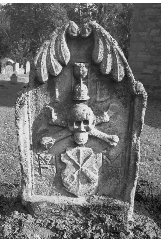 Humbie churchyard. James Dobbie d.1679. Stylised leaves curling over top of stone. Hourglass between initials I D. Skull on crossbones. Tools of maltman on a shield between intials M M.