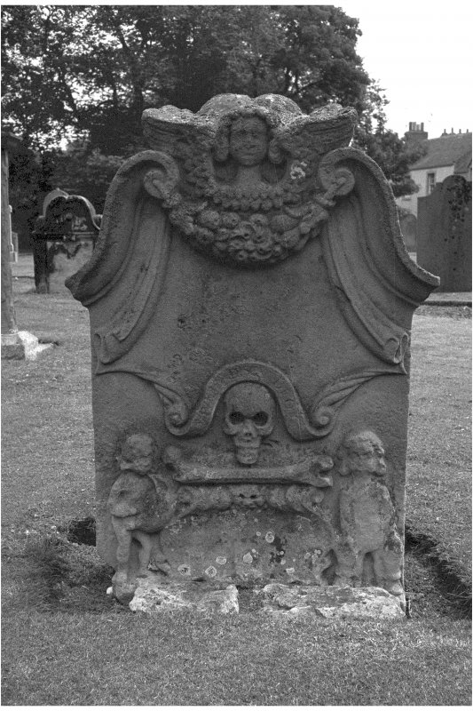 Aberlady churchyard. Inscription illegible. Winged cherub at top of stone, cornucopia beneath. Skull and single bone between figures of sower and reaper.