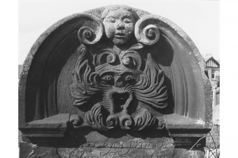 Edinburgh, Kirk Loan, Corstorphine Churchyard. Detail of curved top gravestone, with curled broken pediment, central cherub face, and green-man's face below. Francis Glog, 1739.