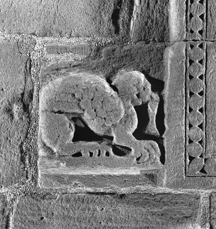 Detail of zoomorphic figure at bottom left hand corner of doorway on West side of tower.