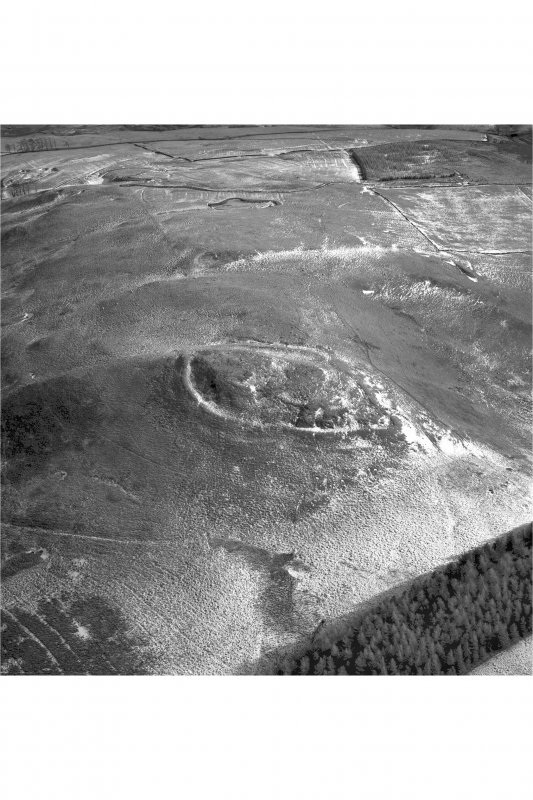 Snaip Hill, oblique aerial view, taken from the W, centred on the remains of fort, enclosure and possible hut circle.