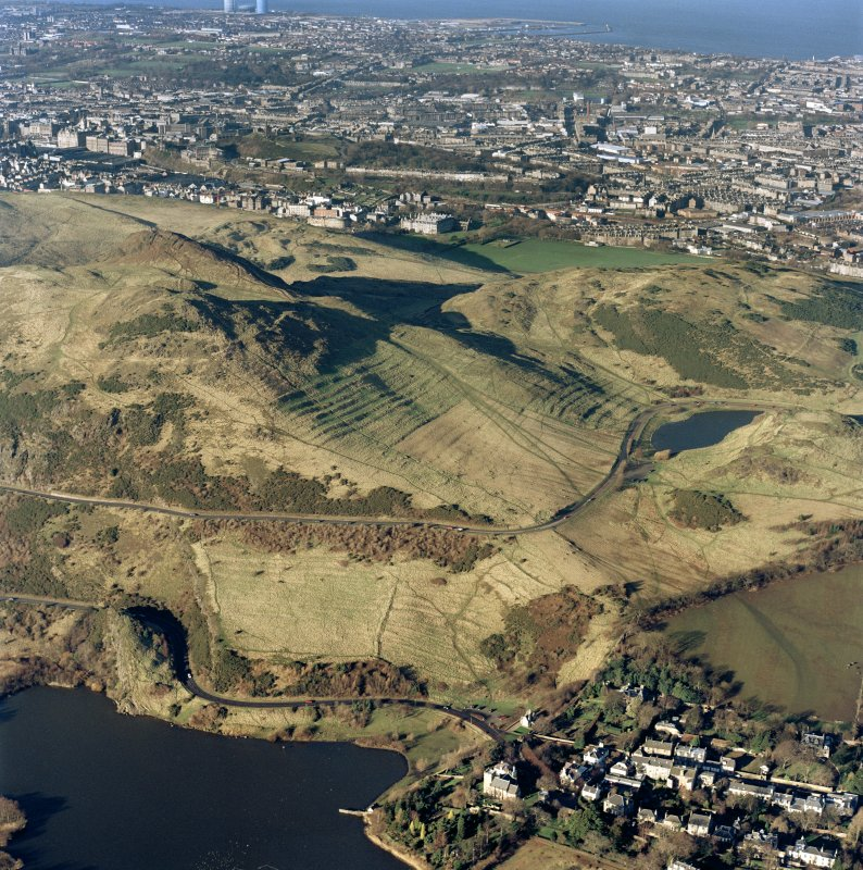 Oblique aerial view of Holyrood Park centred on the remains of cultivation terraces, taken from the SE.