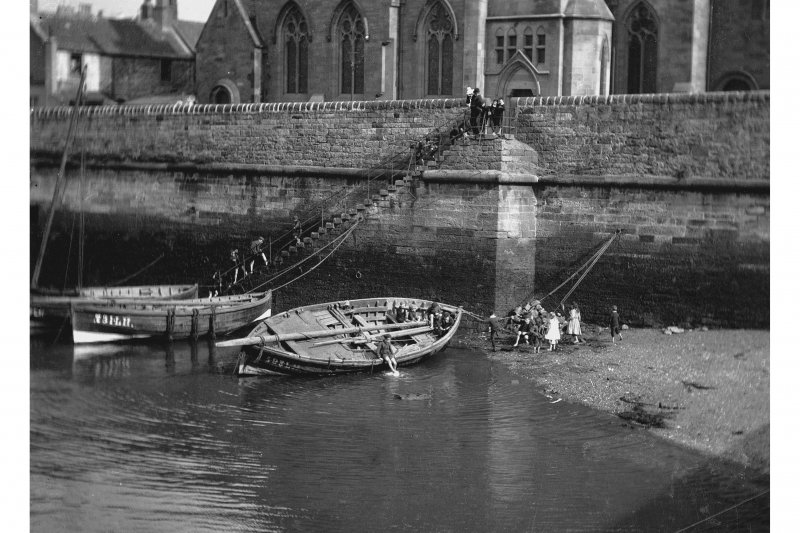 Newhaven Harbour. View of children playing in fishing boats by harbour wall in front of Newhaven Free Church, Pier Place, at low tide.
