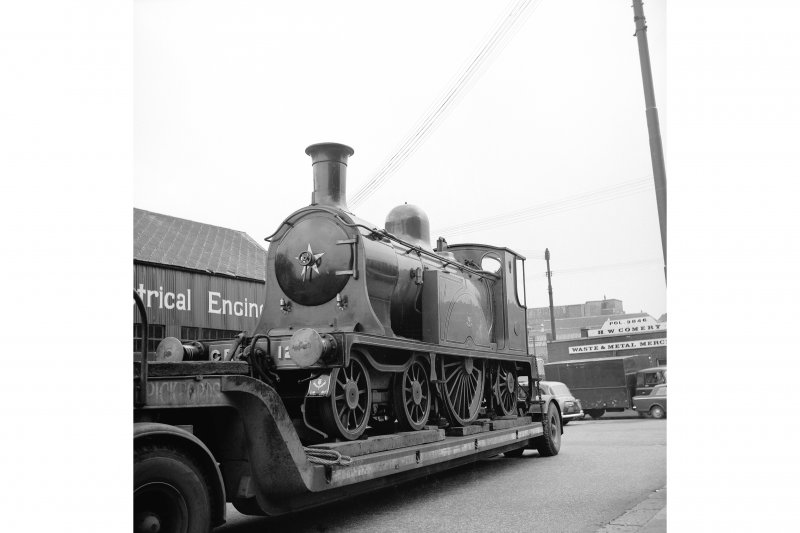 Glasgow, 6 Albert Drive, Engineering Works View from W showing locomotive number 123 on trailer with part of engineering works to left and scrap metal merchant in background