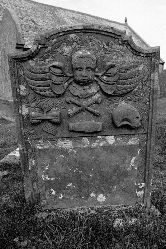 Gravestone commemorating Ann Williamson, d.1780. Winged cherub; winged hourglass, crossbones, coffin, skull in profile.