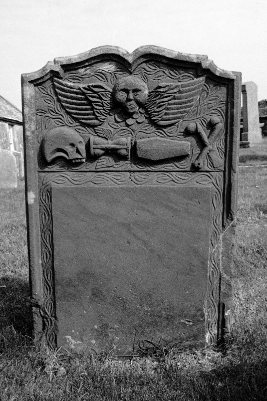 Gravestone commemorating Isobel McLunie, d.1769. Winged cherub; skull in profile, coffin, winged hourglass, crossbones.