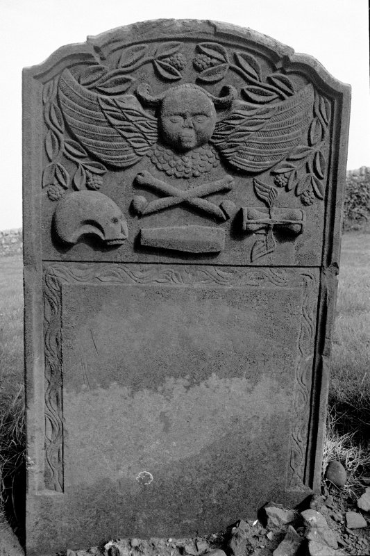 Gravestone commemorating Elizabeth McKittrick, d.1751. Winged cherub; skull in profile, crossbones, coffin, winged hourglass.