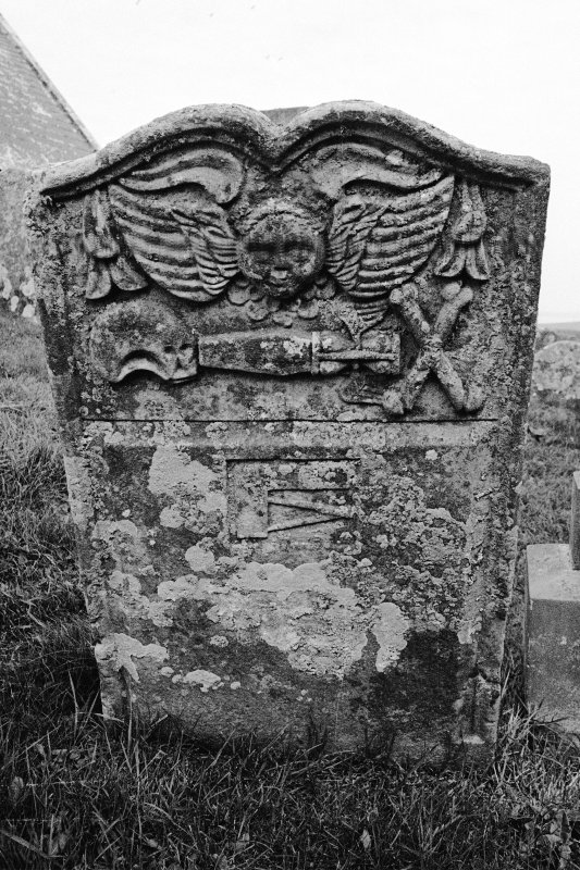 Gravestone dated 1760. Winged cherub; skull in profile, coffin, winged hourglass, crossbones; set-square and compasses.