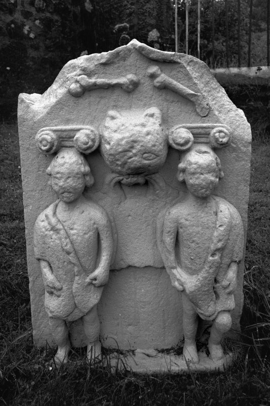 Muirkirk Old Parish Church. No date or inscription. Pair of single bones; large feline head flanked by youthful caryatids with Ionic capitals.