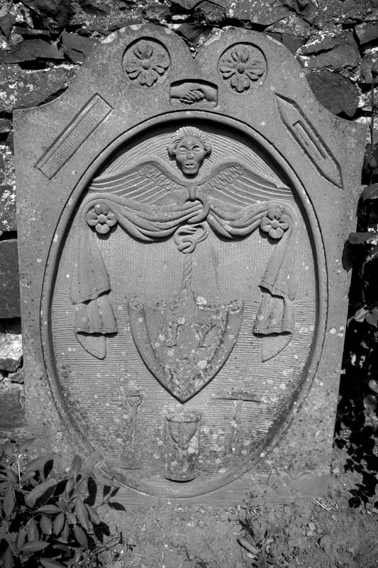Gravestone dated 1831. Pair of rosettes, clasped hands, weaver's shuttle and reed; winged cherub, shield containing intials 'J Y'; spade, hourglass and turf-cutter.