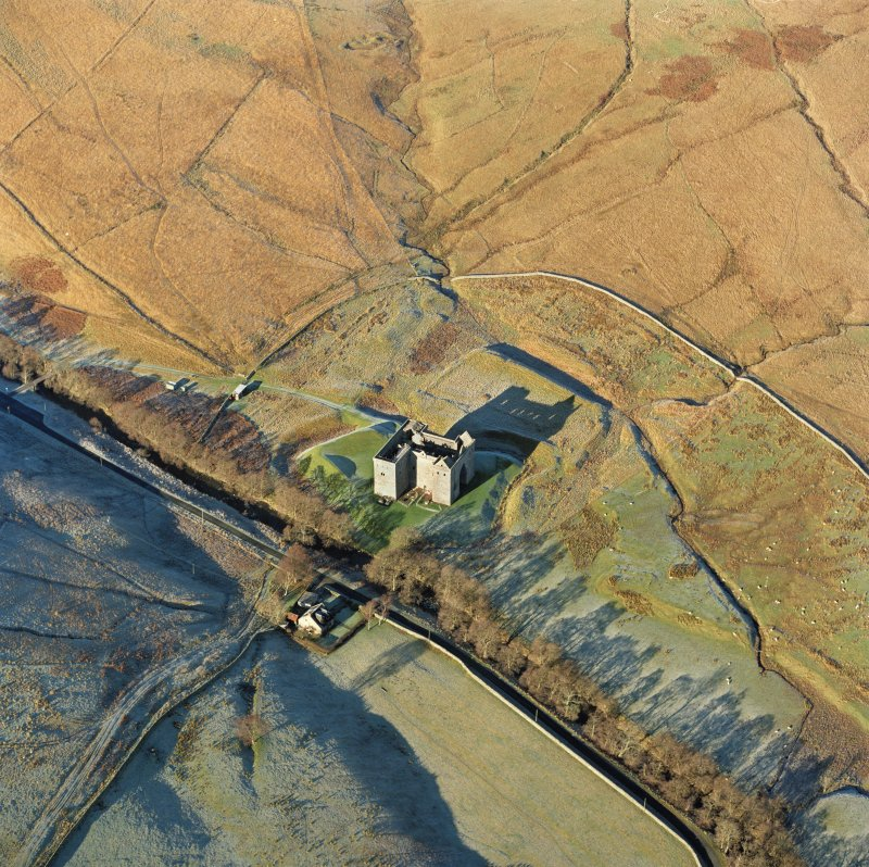Hermitage castle, oblique aerial view from the SE showing the outworks, early earthwork castle and the park pale in the background.