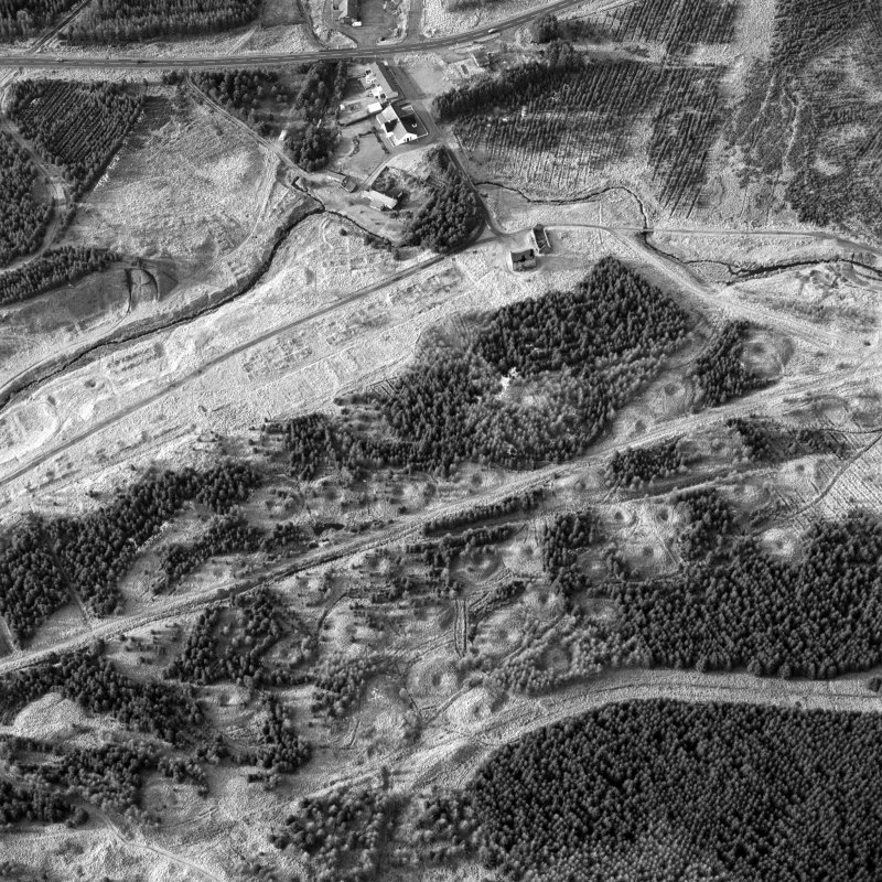 Scanned image of oblique aerial view, taken from the ESE, showing the remains of workers' rows and buildings across the centre of the photograph, lime kilns in the centre left, and a large area of bell pits in the bottom half. Digital image of C41142.