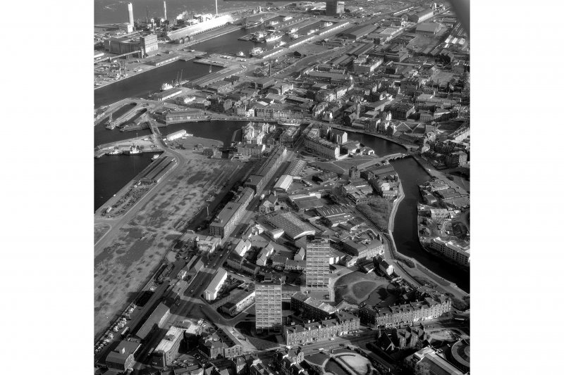 Scanned image of an oblique aerial view showing part of the docks and a view to Arthur's Seat..