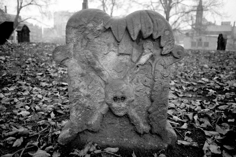 North Leith Burial Ground. View of gravestone, Hutton, leaves fringe top of stone, skull over bones.
