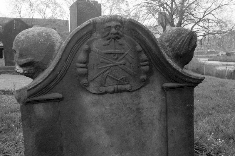 North Leith Burial Ground. View of gravestone, Home, green man holds anchor in mouth, heads on shoulders of headstone.
