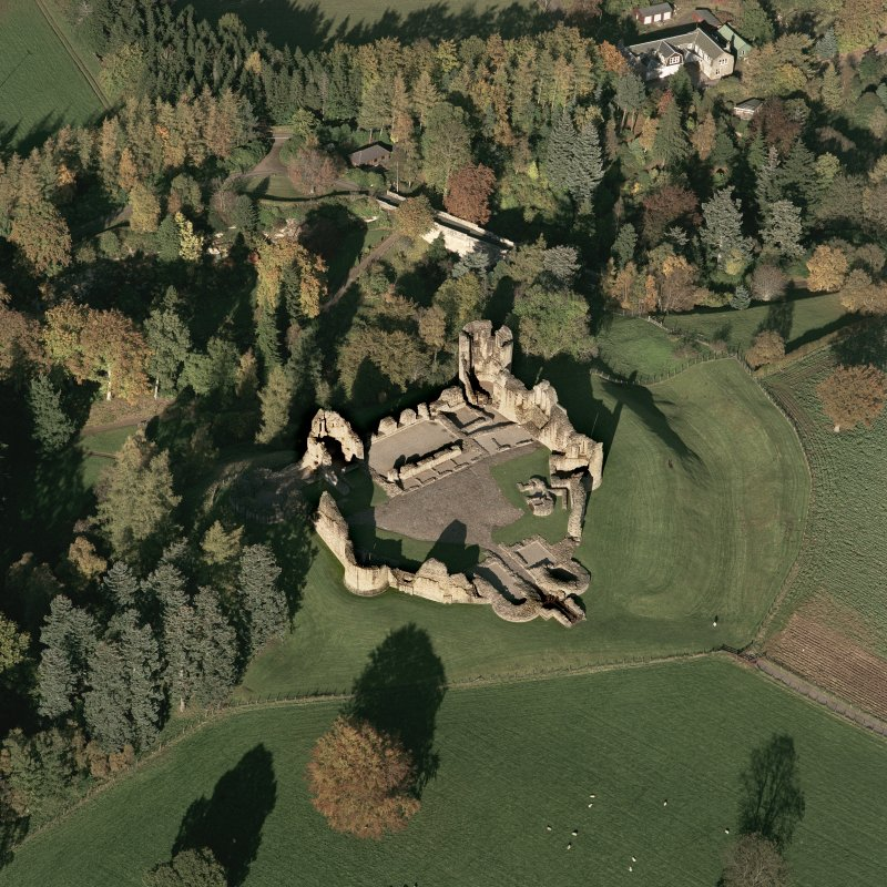 Oblique aerial view of Kildrummy castle centred on the remains of the castle, taken from the SW.