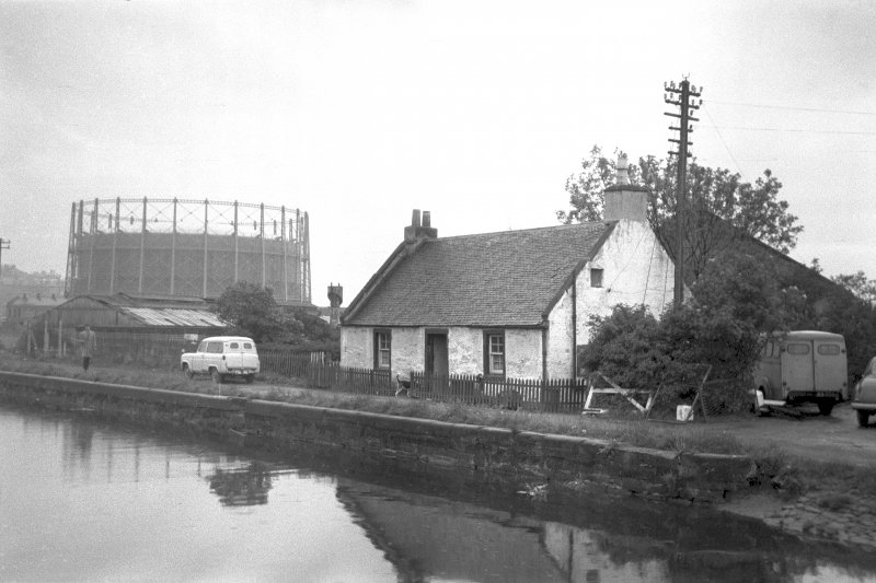 View from NNW showing WNW and NNE front of lock-keeper's cottage with gasholder in background