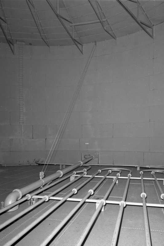 Circular oil-storage tank, interior. Detail showing steam pipes on the floor and floating outlet pipe.