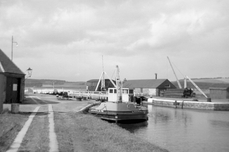 View from SSE showing workboat at N end of Muirtown Basin with smithy on left and crab winch and workshops in background