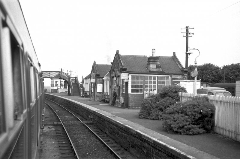 View from S showing part of WSW and SSE fronts of main station building with part of up platform shelter, footbridge and signal box in background