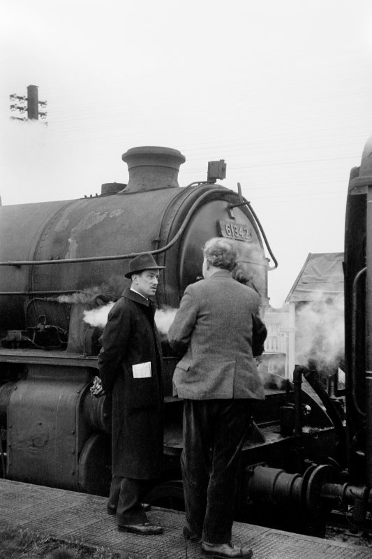 View showing men talking beside locomotive at Bogside Station