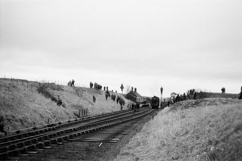 Distant view from NE showing train at station with people running in all directions