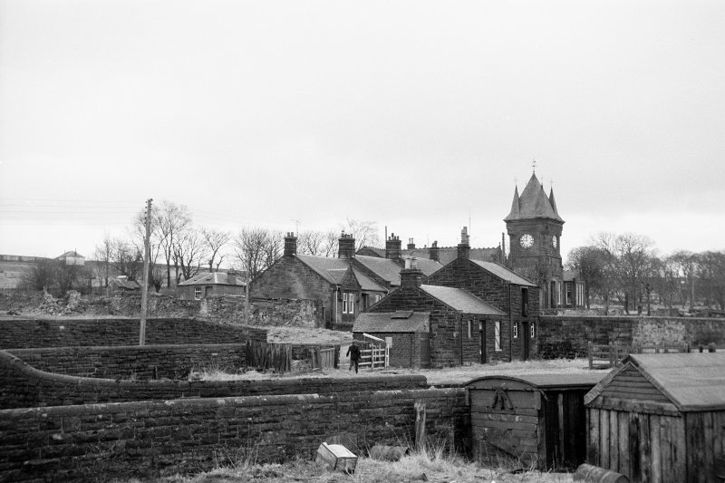 View from N showing NNE and WNW fronts of Station Cottage with Ironworks Cottages and Institute in background