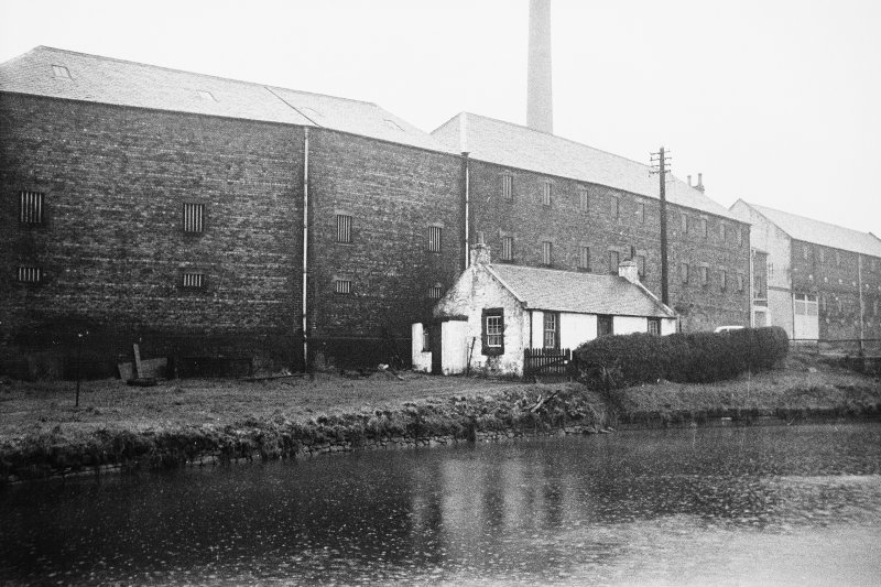 View from NNE showing ENE front and part of NNW front of cottage with distillery in background