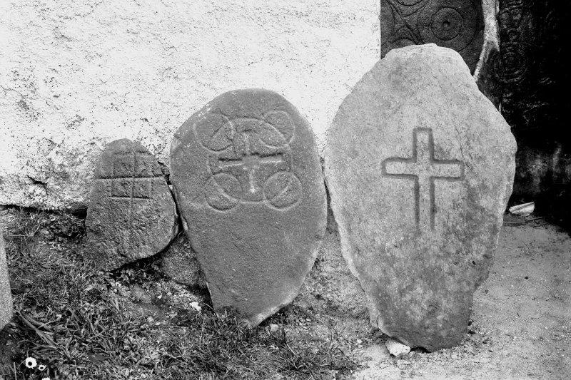 View of cross-incised stones. Original negative captioned: 'Ancient Stone Crosses at Old Church of Dyce May 1903'.