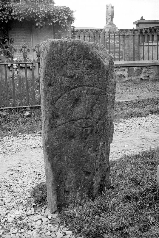 Pictish symbol stone standing in kirkyard. View of reverse, showing three circles, crescent and V-rod, and cup-marks. Half-plate glass negative.